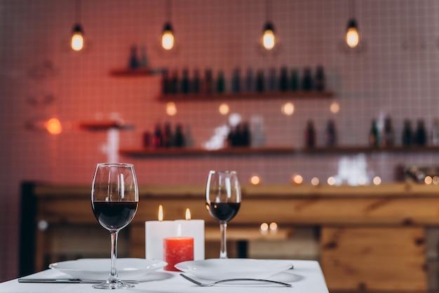 Zwei gläser mit rotwein und brennenden kerzen auf einer gedienten tabelle in einer restaurantnahaufnahme Premium Fotos