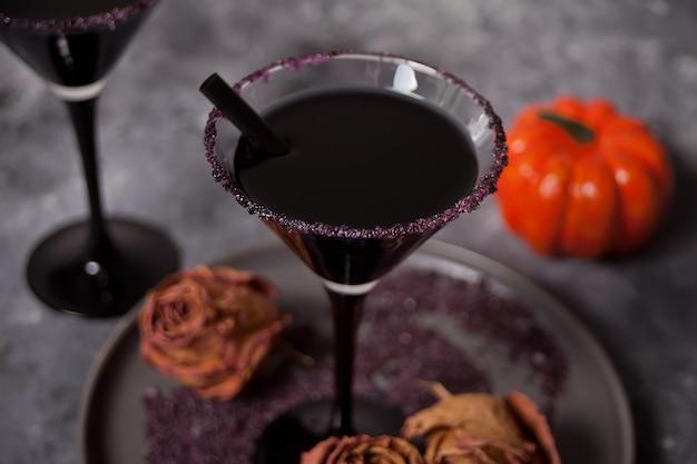 Zwei gläser mit schwarzem cocktail, getrocknete rosen für halloween-party auf dunkelheit Premium Fotos
