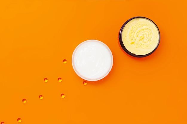 Zwei gläser mit verschiedenen cremes auf orangefarbenem hintergrund, daneben kapseln mit vitamin e. Premium Fotos