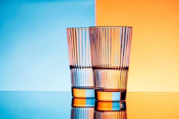 Zwei gläser mit wasser über blauem und orange hintergrund. Kostenlose Fotos