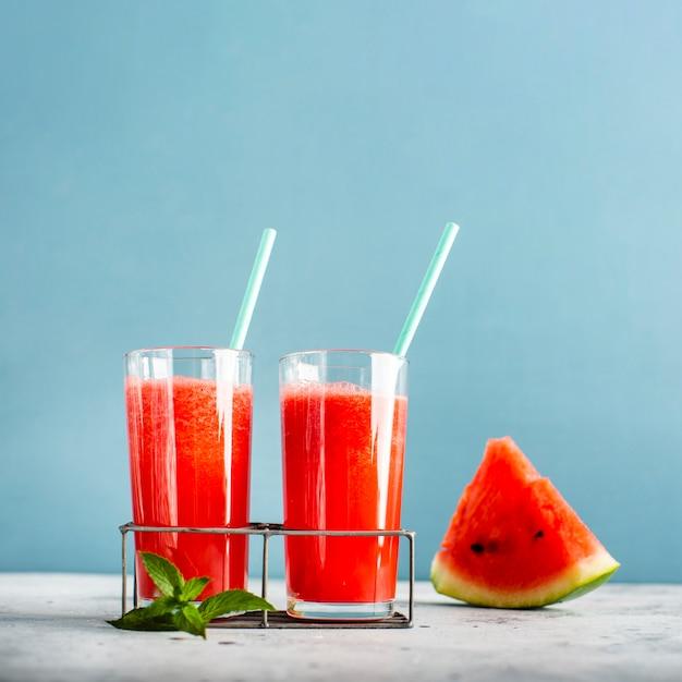 Zwei gläser mit wassermelonensaft und scheibe daneben Kostenlose Fotos