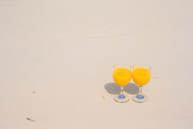 Zwei gläser orangensaft auf tropischem weißem strand Premium Fotos