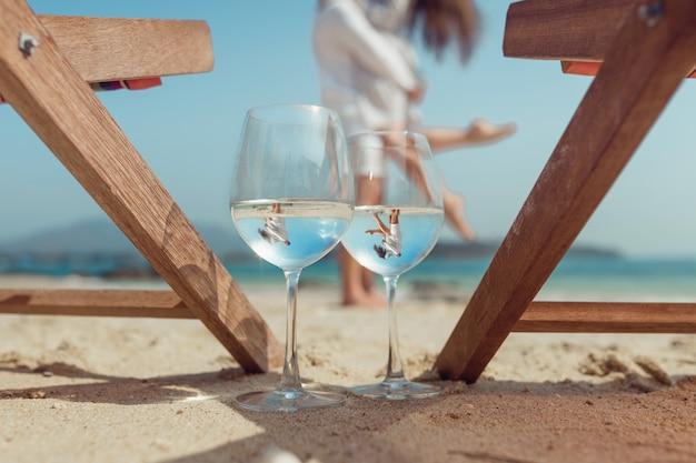 Zwei gläser reflektieren das umarmende paar am strand. flitterwochen. schöne reflexion in einem glas wein. sommerferien. tropischer urlaub Premium Fotos