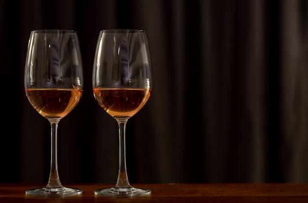 Zwei gläser rosenwein auf holztisch, zum für ein paar zu feiern. Premium Fotos