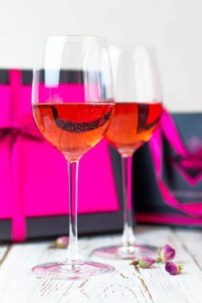 Zwei gläser roséwein auf weißem holztisch mit rosa geschenkboxen Kostenlose Fotos