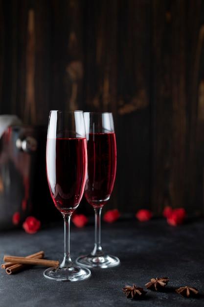 Zwei gläser roter champagner auf dunklem hintergrund. geschenk für frauen. frauenurlaub. Premium Fotos