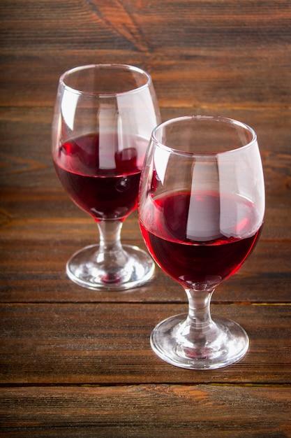 Zwei gläser rotwein auf einem braunen holztisch. alkoholische getränke. Premium Fotos