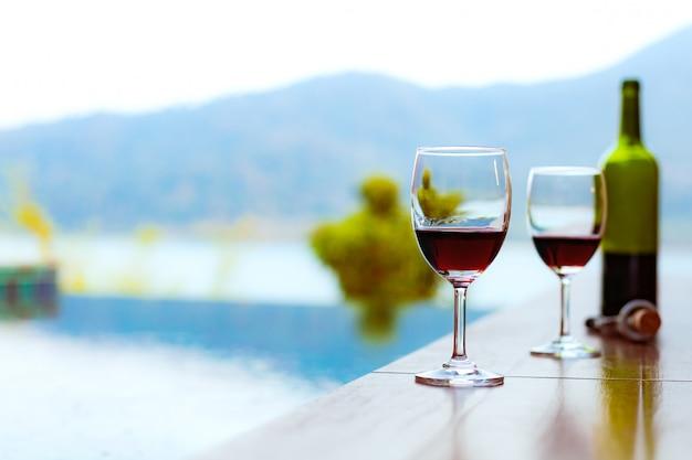 Zwei gläser rotwein in der nähe des swimmingpools mit einem spektakulären blick auf das meer Premium Fotos