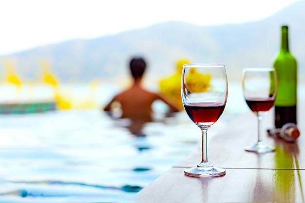Zwei gläser rotwein nahe dem swimmingpool mit einem mann schwimmt im pool Premium Fotos