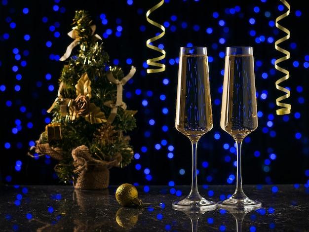 Zwei gläser sekt und ein weihnachtsbaum auf blauen bokeh-lichtern. silvester Premium Fotos