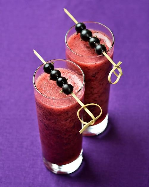 Zwei gläser smoothies der schwarzen johannisbeere auf lila leinenhintergrund Premium Fotos