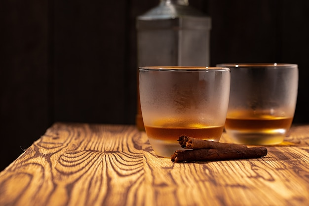 Zwei gläser whisky und zigarren auf holztisch schließen oben Premium Fotos