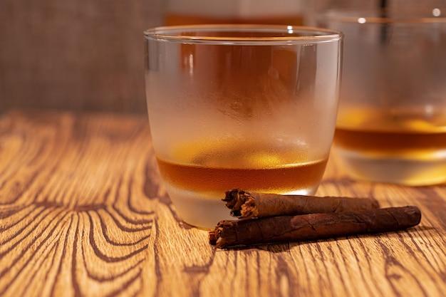 Zwei gläser whisky und zigarren auf holztisch Premium Fotos
