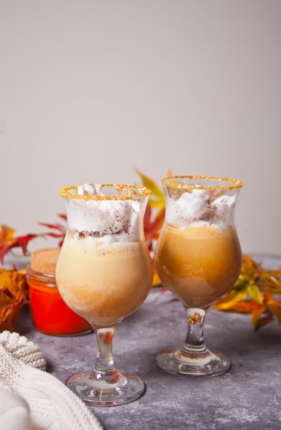 Zwei glas heißer sahniger kakao mit schaum mit herbstlaub und kürbisen auf dem hintergrund Premium Fotos