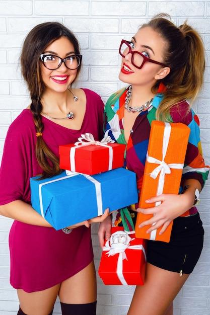 Zwei glückliche beste freunde, die helle geschenke und geschenke halten Kostenlose Fotos