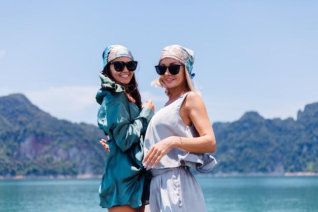 Zwei glückliche blogger-touristenfreunde in seidenanzug und schal und sonnenbrille im urlaub reisen um thailand auf asiatischem boot, khao sok nationalpark. Kostenlose Fotos
