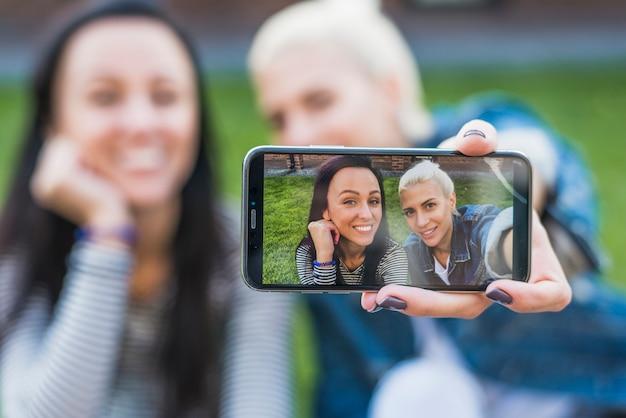 Zwei glückliche frauen, die selfie am handy nehmen Kostenlose Fotos
