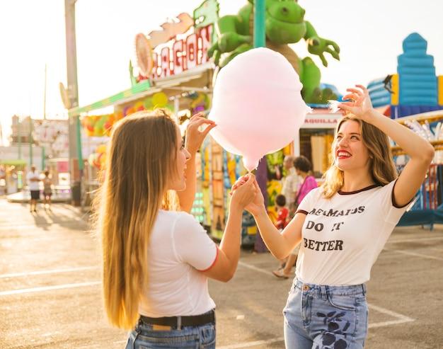 Zwei glückliche frauen, die süßigkeitsglasschlacke am vergnügungspark halten Kostenlose Fotos