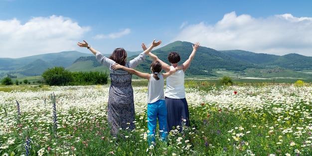 Zwei glückliche frauen mit einem teenager-mädchen, das hände hoch genießt, genießen schönen blick auf die blühende wiese nahe bergen in armenien am sommertag. blick von hinten Premium Fotos