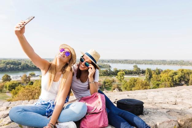 Zwei glückliche freundinnen, die selfie auf mobiltelefon nehmen Kostenlose Fotos