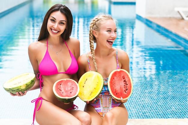 Zwei glückliche hübsche frau, die spaß nahe pool am sommerfest hat, wassermelonen hält und badeanzüge trägt Kostenlose Fotos