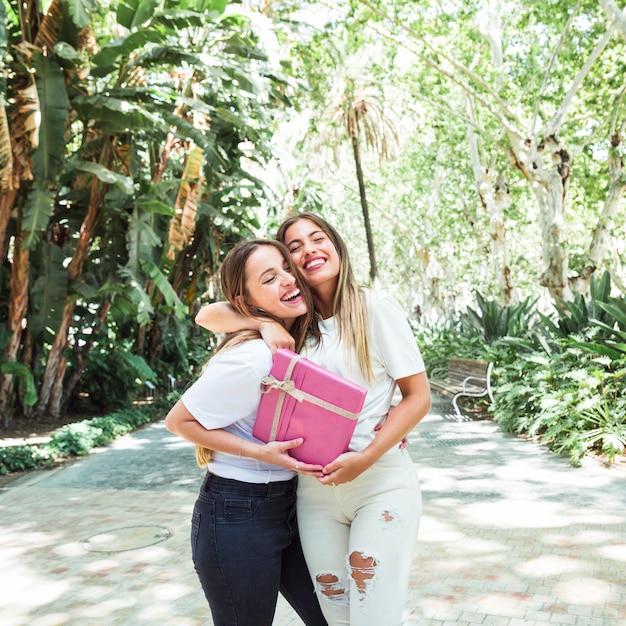 Zwei glückliche junge frauen mit der rosa geschenkbox, die im park steht Kostenlose Fotos