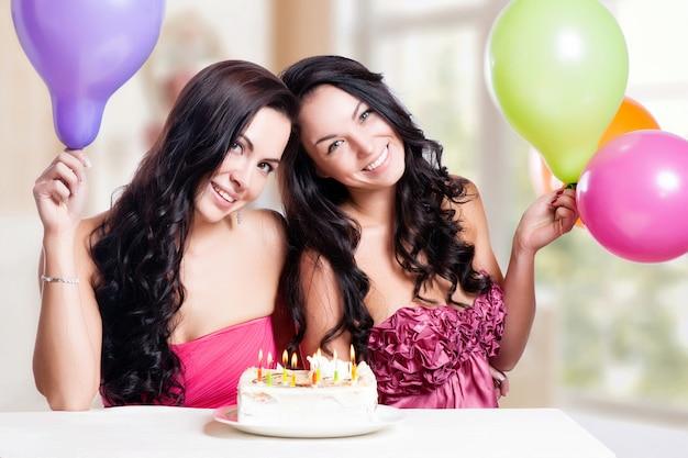 Zwei glückliche junge frauen mit kuchen Premium Fotos