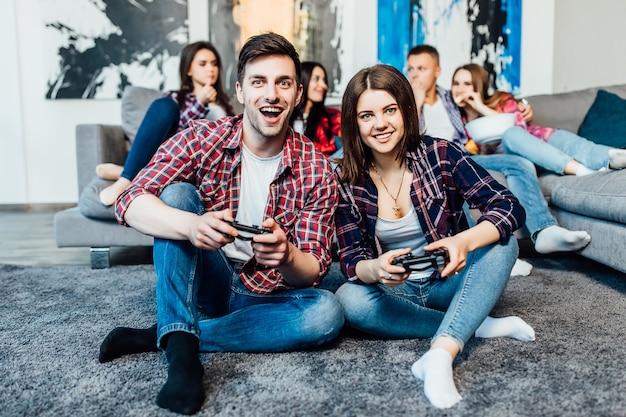 Zwei glückliche junge freunde, die joystick halten und videospiel spielen. fröhliche zeit Premium Fotos