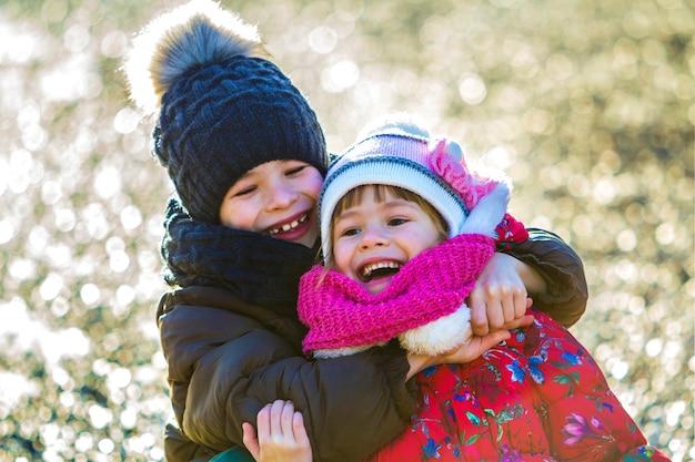 Zwei glückliche kinderjungen und -mädchen, die draußen im sonnigen wintertag spielen Premium Fotos