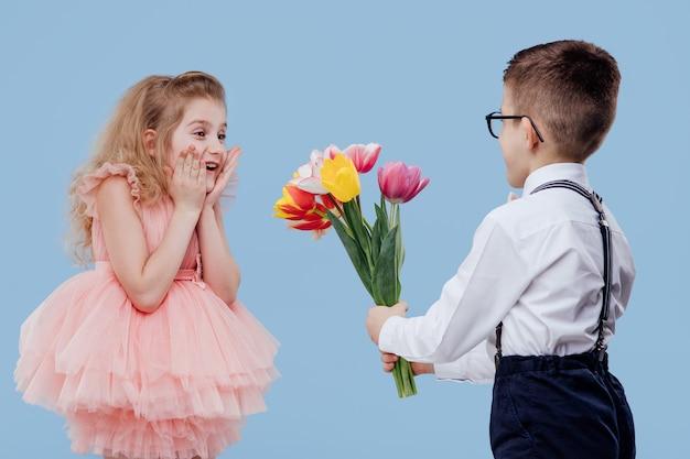 Zwei glückliche kleine kinder. kleiner junge streckt blumen zu einem kleinen mädchen, isoliert auf blauer wand Premium Fotos