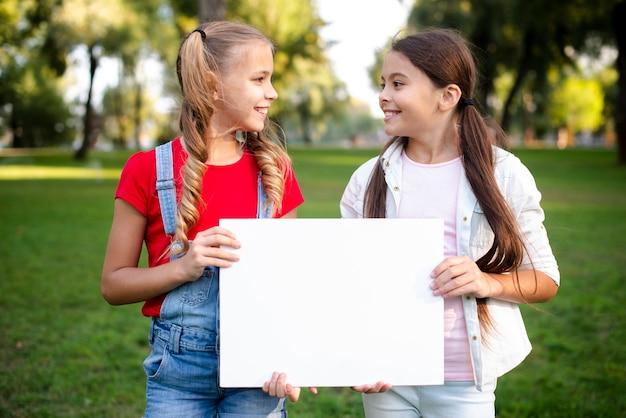 Zwei glückliche mädchen, die ein papier in ihren händen halten Kostenlose Fotos