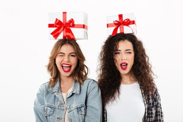 Zwei glückliche mädchen, die geschenke auf ihren köpfen halten, während an der kamera über weißer wand blinzelt Kostenlose Fotos