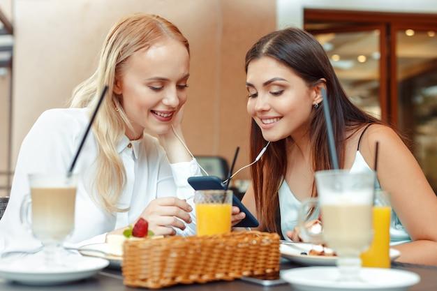 Zwei glückliche mädchen, die zusammen musik mit geteilten kopfhörern im netten café hören. genießen sie musik und unterhaltung Premium Fotos