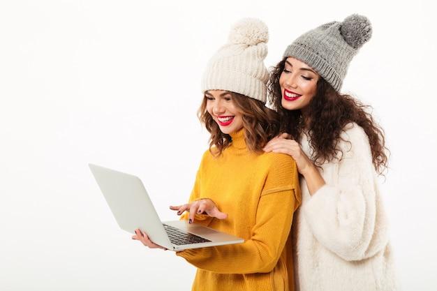 Zwei glückliche mädchen in den strickjacken und in hüten, die zusammen bei der anwendung der laptop-computers über weißer wand stehen Kostenlose Fotos