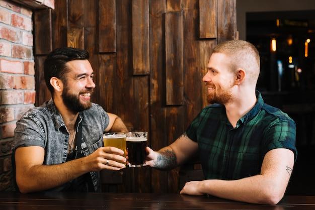 Zwei glückliche männliche freunde, die alkoholische gläser in der stange rösten Kostenlose Fotos