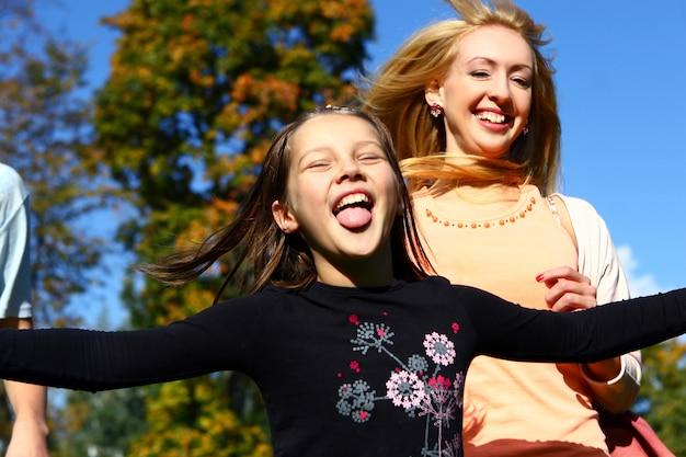Zwei glückliche schwestern haben spaß im park Kostenlose Fotos