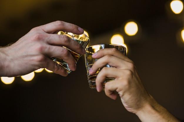 Zwei hände, die whisky gegen belichteten hintergrund rösten Kostenlose Fotos