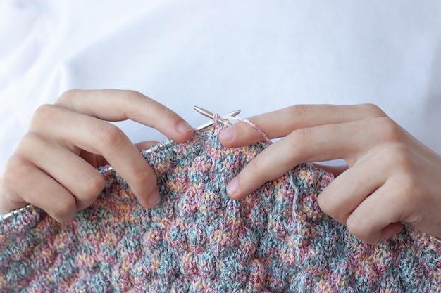 Zwei hände halten stricknadeln und stricken Premium Fotos
