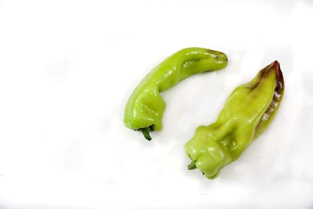 Zwei hässliche lustige grüne paprika lokalisiert auf weißem hintergrund. vegetarisches lebensmittelkonzept. speicherplatz kopieren. Premium Fotos