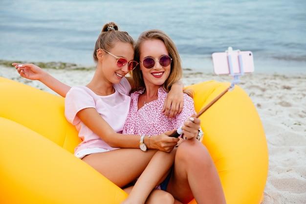 Zwei herrliche lächelnde mädchen in der sonnenbrille, die ein foto auf selfie stock macht Kostenlose Fotos