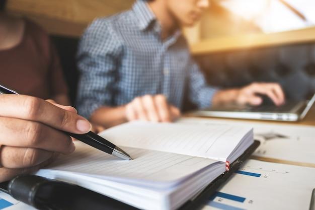 Zwei hochschulstudenten, die zusammen mit laptop- und prüfungsdokumenten in einem café / in einer bibliothek arbeiten Premium Fotos