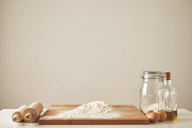 Zwei hölzerne nudelhölzer, olivenöl extra vergine, transparentes glas und hölzernes schneidebrett mit weißmehl, chiken-eier isoliert. alles für die teighaltung vorbereitet Kostenlose Fotos