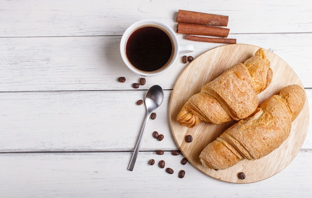 Zwei hörnchen mit tasse kaffee auf hölzernem küchenbrett auf weißem hölzernem hintergrund Premium Fotos