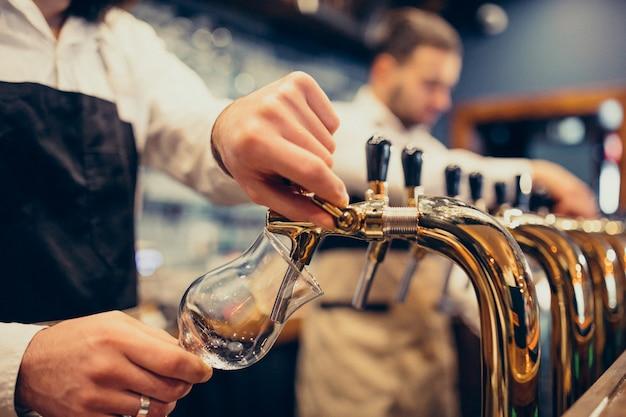 Zwei hübsche barmixer, die bier an der kneipe poring sind Kostenlose Fotos