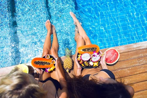 Zwei hübsche blonde und brünette mädchen, die spaß haben und verrückt werden bei tropischer fruchtparty, sexy schwarzer bikini, viel süßes veganes essen, exotischer urlaub, posieren in der nähe des pools, sommermodebild. Kostenlose Fotos