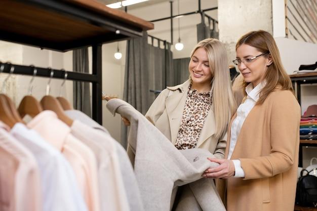 Zwei hübsche frauen in schicker freizeitkleidung, die einen eleganten hellgrauen mantel betrachten, während sie einen in der zeitgenössischen boutique zur freien verfügung wählen Premium Fotos
