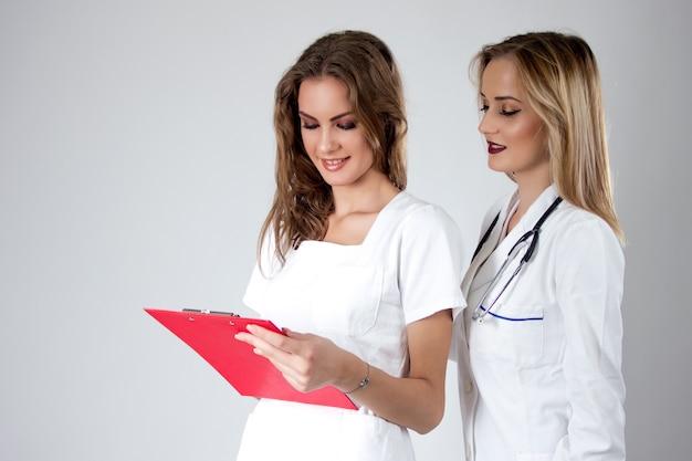 Zwei hübsche junge frauen ärzte, krankenschwestern suchen durch die patientin krankenschwester. Kostenlose Fotos