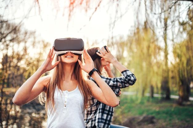 Zwei hübsche mädchen genießen die gläser der virtuellen realität, die im freien sind Premium Fotos