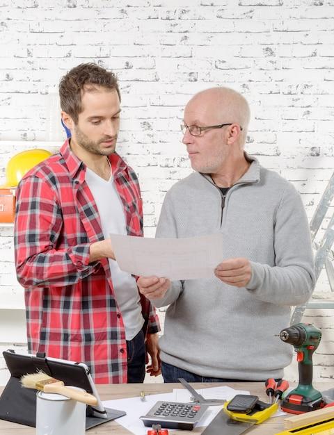 Zwei ingenieure, die einen plan im büro lesen Premium Fotos