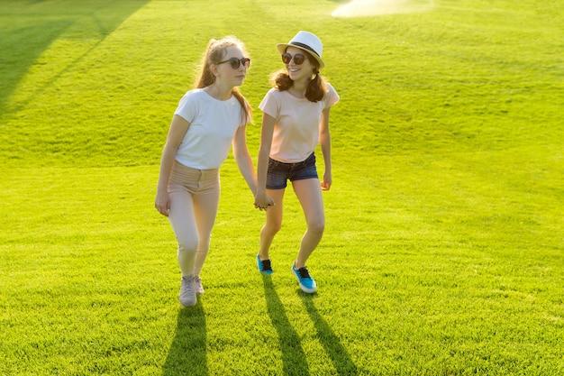 Zwei jugendlich mädchen halten hände auf dem grünen gras im park an einem heißen sommertag Premium Fotos